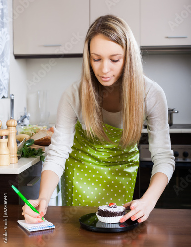 Blonde girl weighing cakes on kitchen scales