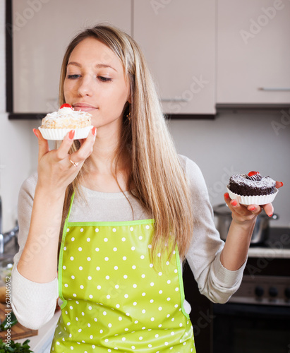 Pretty housewife in apron with cakes