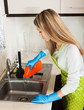 housewife pouring detergent into  sink