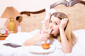 young blond woman lying in bed biting donut