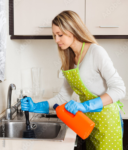 woman  cleaning pipe   in kitchen