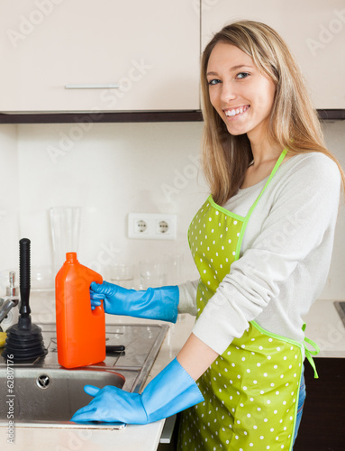 Young woman cleaning pipe with detergent