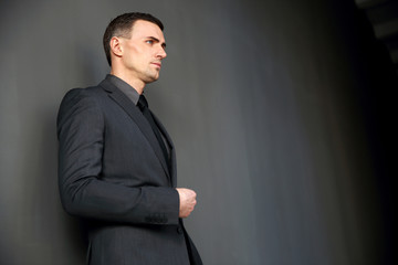 Pensive businessman standing and looking away on gray background