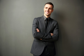 Cheerful businessman with arms folded standing