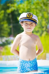 Cute boy happy with sailor cap in swiming pool