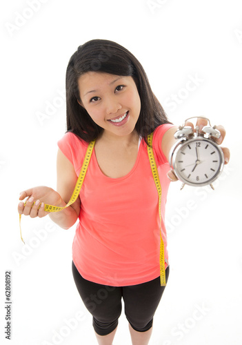 asian woman happy about starting a diet holding alarm clock