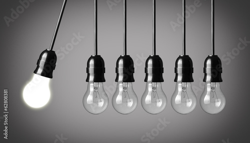 Perpetual motion with light bulbs. Idea concept on gray backgrou