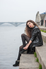 Portrait of young woman in the city near the river