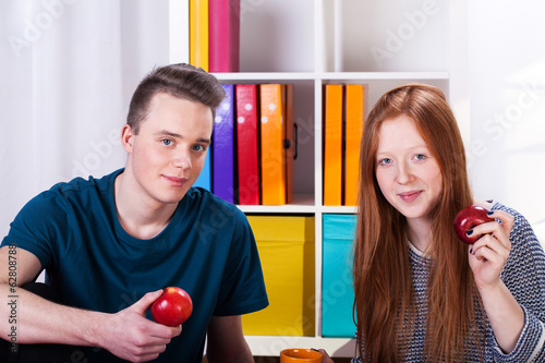 Teenage friends eating apple