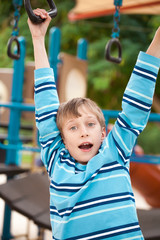 Beautiful cheerful child playing on playground in summer