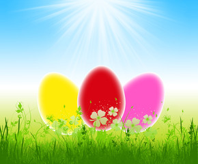 Three colorful easter eggs in the grass on blue sky background