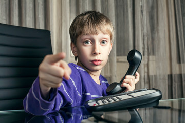 Cute funny child sitting in office making phone call
