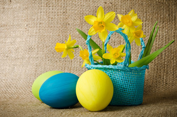Easter eggs and daffodils in a basket