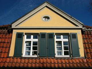 Mansarde mit spitzem Giebel und grünen Fensterläden