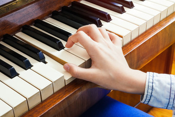 Closeup of child's hand palying piano