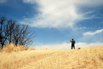 Man standing in a field observing the horizon