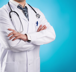 Male doctor therapist wearing lab coat over blue background