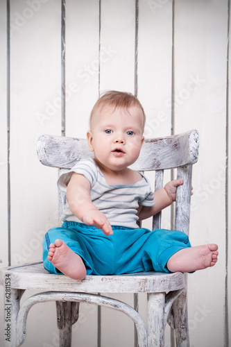 Baby boy sitting on chair in vintage interior