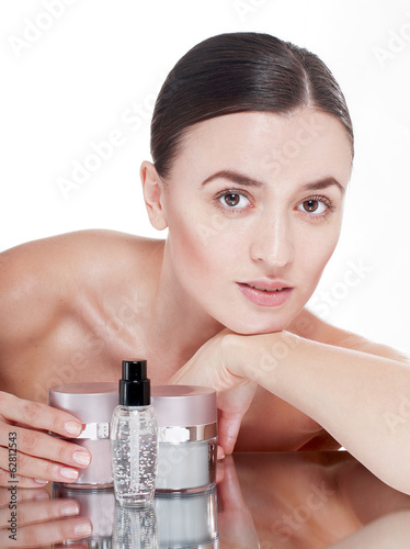 Young woman with  a well-groomed skin near the creams cosmetics.
