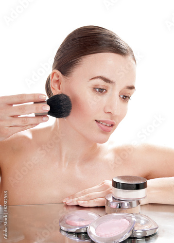 Beautiful girl applying  blusher by brush on her face - isolated