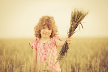 Happy kid holding wheat