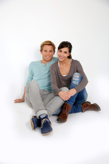 Cheerful young couple sitting on floor, isolated