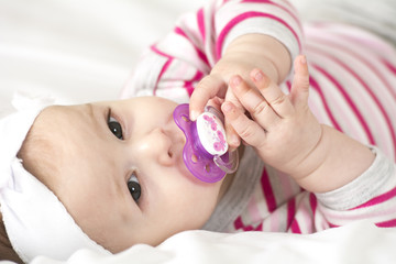 cute baby with pacifier lying in a cradle on a white background