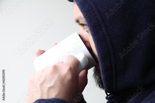 Man in hoodie drinking coffee