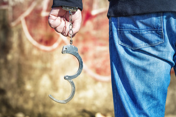 Man with handcuffs near the old wall