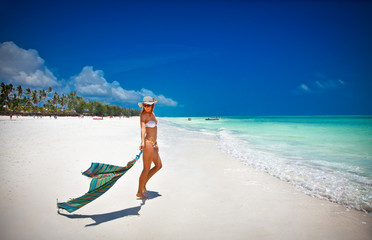 Fashion woman relax on the beautiful tropical beach in Africa.