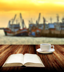 Read book with coffee cup beside jetty
