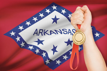 Medal in hand with flag on background - State of Arkansas.
