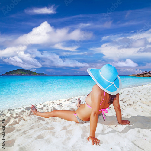 Woman in hat relaxing on holiday at the sea