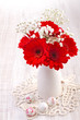 Red gerbera flowers in vase and easter candy