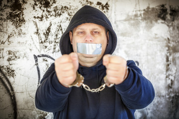 Hostage in handcuffs with tape on the mouth