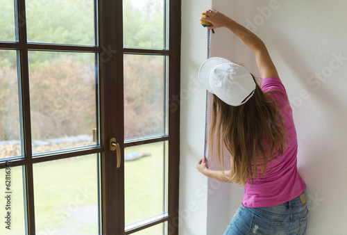 Woman measuring the wall