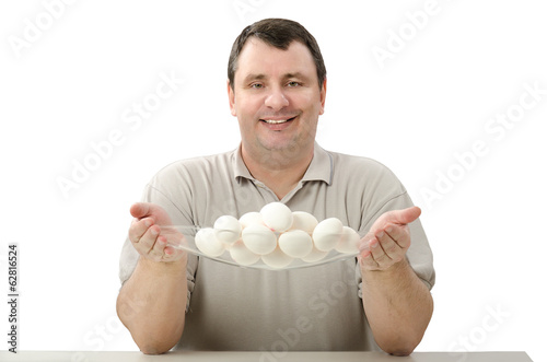 Smiling farmer holding a glass basket of eggs