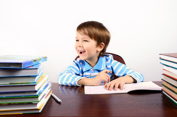 laughing boy sitting at the desk with many books