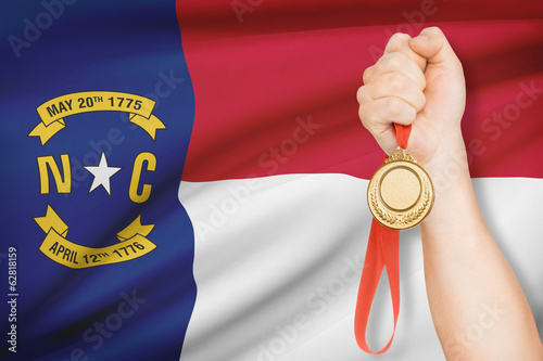 Medal in hand with flag on background - State of North Carolina.