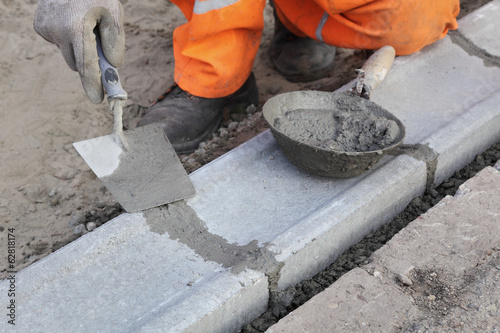 Worker installing curb stone, using trowel and mortar