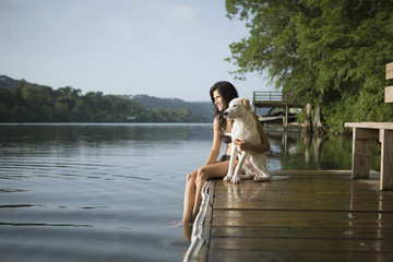 A woman with her arm around a small white dog on a jetty on a lake.