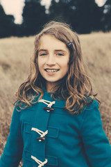 A young girl of nine years old, in a blue duffle coat, smiling at the camera.