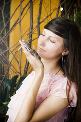 Portrait of beautiful girl with lizard in a greenhouse