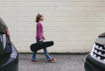 A ten year old girl carrying a violin in a case on an urban street.