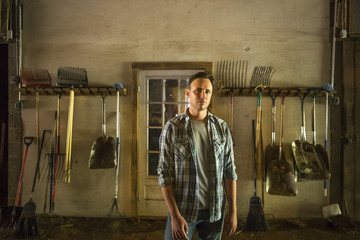 An organic farm in the Catskills. A man standing in a barn with equipment stored around the walls.