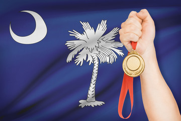 Medal in hand with flag on background - State of South Carolina.