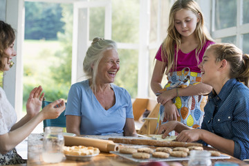 Farmhouse in the country in New York State. Four generations of women in a family baking together.