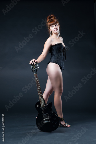 Young nude woman with an electric guitar in the studio