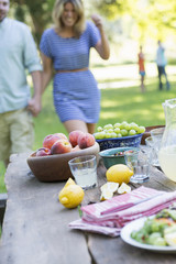 A summer buffet of fruits and vegetables, laid out on a table. People in the background.