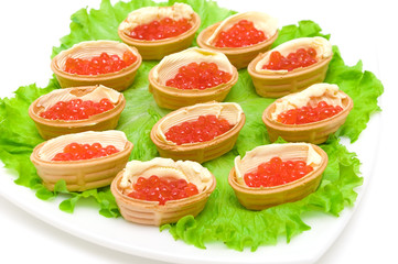 Tartlets with red caviar on a plate on white background